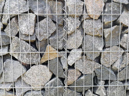 Gabion, metal basket filled with thick stones 写真素材