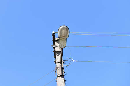 Old concrete electric pole for transmission of wired electricity with lamp post on a background of a cloudy blue sky. Obsolete me. Thod of supplying electricity. Stock fotó