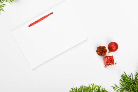 notebook with pen on christmas background. Empty white notebook and pen on white Christmas background of fir branches, cones, gifts. Letter To Santa Claus, mock up. Empty white notebook and pen on a white Banco de Imagens