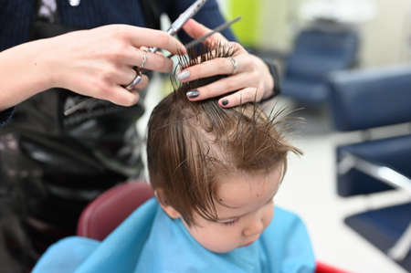 A child at the hairdresser. The first haircut of the child at the hairdresser. Baby haircut toddler.