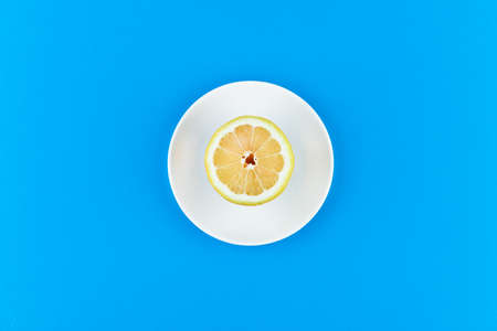 lemon on a blue background. lies on a white plate. half cut lemon. view from above. place to record. Lemon slices on a blue background. In summer, cool slices of orange. Lime, fruit, refreshing, yellow, vibrant, citrus, diet. 写真素材