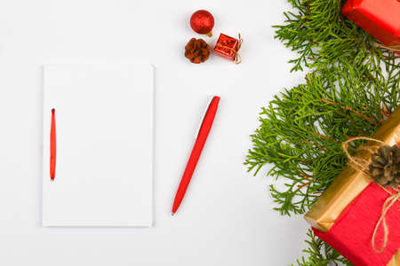 Blank white notebook and red pen on christmas white background. Christmas fir branches, cones, gifts. Letter to Santa Claus, mock up. Blank white notebook and red pen on white.