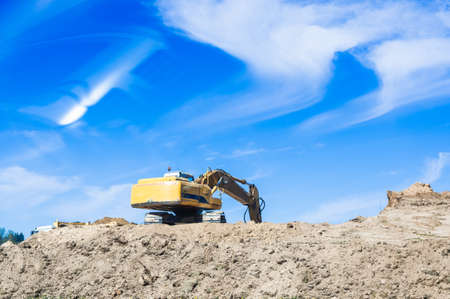 Construction excavator on a background of blue sky.