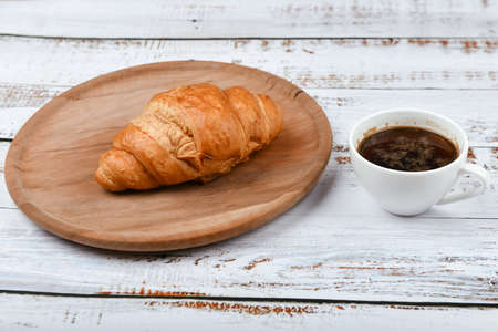 croissant and cup of coffee on a white wooden table. Fresh french croissant. on a wooden background. View from above. Morning breakfast with a croissant. French breakfast Prepared at home