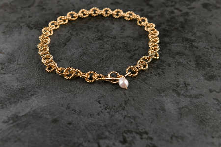 gold chain with pearls against black background. place for an inscription. golden chain on marble. ring gold plate