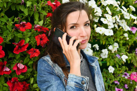 Girl holds a phone on a background of flowers