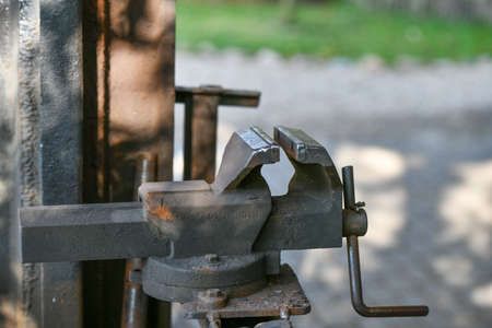 blacksmith's clamp. Metal clamping device on an old workbench. Vise desktop.