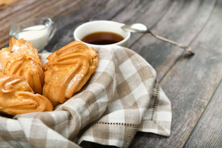 Choux cake with coffee on a wooden background. In a basket on a checkered towel. View from above. Chic with cottage cheese. Small custard cakes in wicker bowl on wooden background