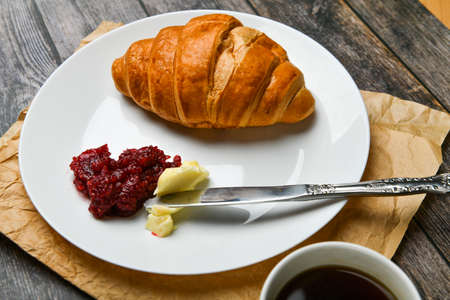 Kurasan with butter and jam. the beginning of the morning. A cup of coffee. Fresh french croissant. Coffee cup and fresh baked croissants on a wooden background. View from above 스톡 콘텐츠