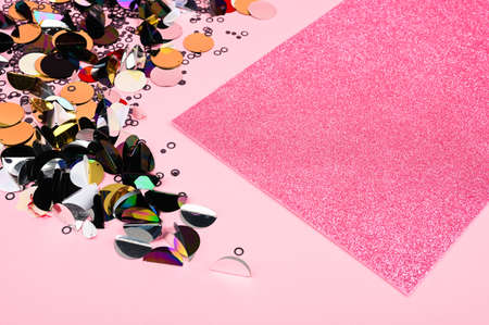 Creative layout made of sequins decor and pink glittr card. A beautiful foundation for sites, layouts and postcards. Flat lay, top view. 免版税图像