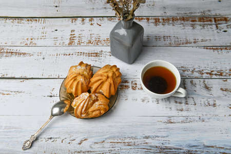 morning coffee with sweets. with cream filling. flat lay. on a light wooden table