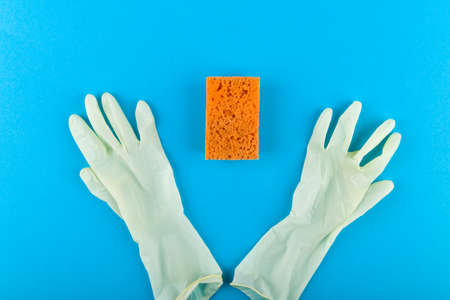 White gloves and a sponge. on a blue background. House cleaning. View from above.