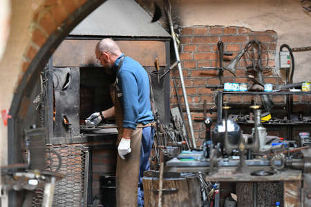 An experienced blacksmith works with open fire. A blacksmith extinguishes a flame in a forge with a spark firework, forges hot iron in a workshop