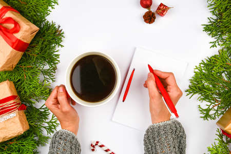 Writes wishes with a coffee mug. Dreams of goals plans make a list for writing new year christmas concept in notebook. Woman hand on a background with fir branches New Year winter holiday Christmas flat lay. Banque d'images