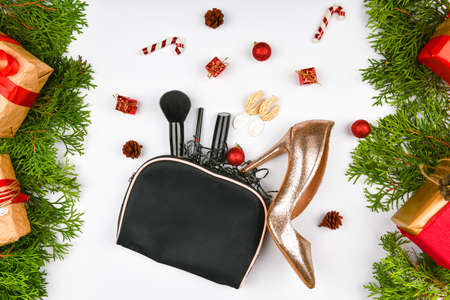 Holiday discounts and shopping concept, flat barking. Christmas composition of women's accessories, cosmetic bag with cosmetics, eyeshadows, face brushes, creams and lotions on a New Year's background