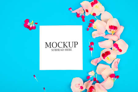 mockup of pink flowers and white paper on a blue background