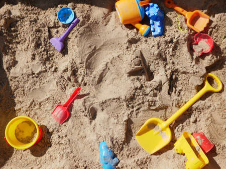 Childrens toys scattered in the sandbox. High quality photo