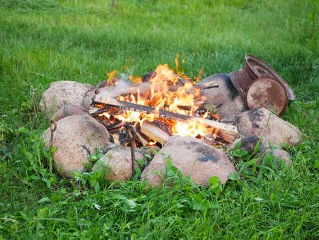 bonfire in stones on green grass. High quality photo Reklamní fotografie