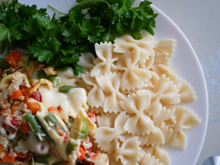 Pasta with freshly prepared vegetables on a plate. High quality photo