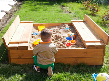 A child spends time playing in the sandbox. High quality photo