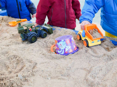 Group of children play in the sandbox.