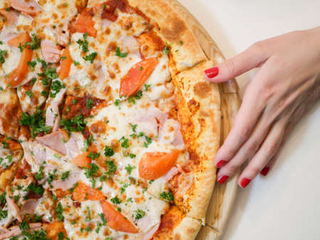 Female hand and pizza. kind of pizza with bacon tomatoes and herbs
