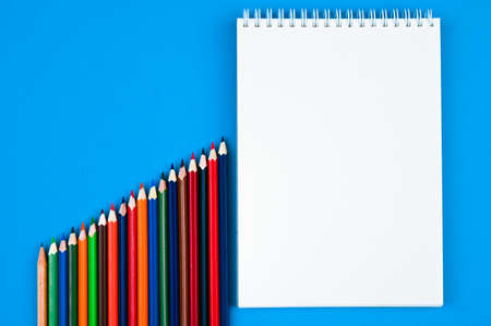 Pencils of rainbow colors and notebooks on a blue background. Concept back to school, drawing. Minimalism, flat lay, copyspace, top view. Reklamní fotografie