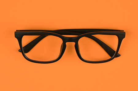 black glasses on an orange background