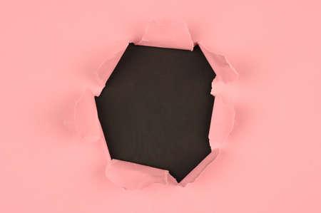 Pink tear paper, on black Reklamní fotografie