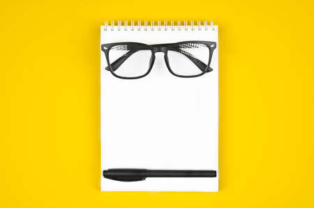 black glasses with a pen on a notebook, on a yellow background Reklamní fotografie - 151447463