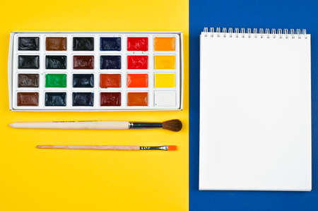multi-colored paints and brushes on a yellow background Reklamní fotografie - 151454116