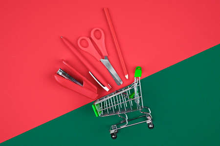 Trolley with red office supplies. On a red-green background. flat lay