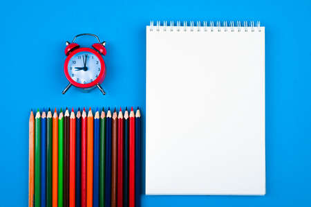 Notebook with colored pencils and a clock Reklamní fotografie