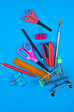Trolley with office supplies on a blue background