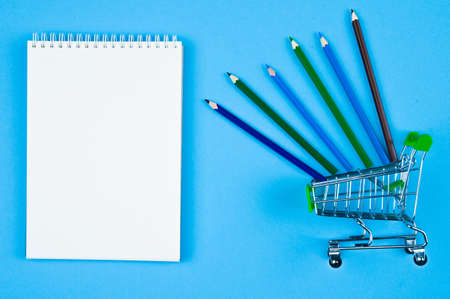 notebook with trolley with pencils on a blue background Reklamní fotografie - 151467694