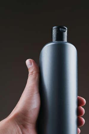 mockup of gray plastic bottle in hands on a dark background Reklamní fotografie - 153076343