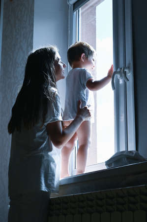 mother and child look out the window in the dark Reklamní fotografie - 153076352