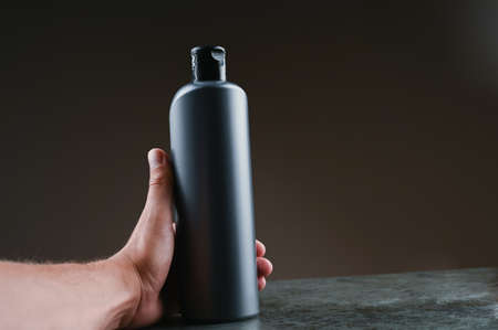 mockup of gray plastic bottle in hands on a dark background