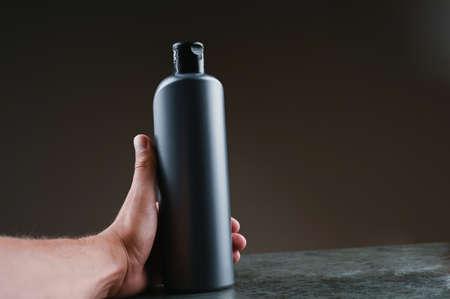mockup of gray plastic bottle in hands on a dark background Reklamní fotografie - 153076359