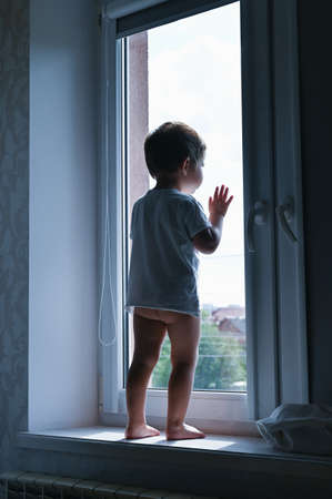 sad child looking out the window Reklamní fotografie - 153076362