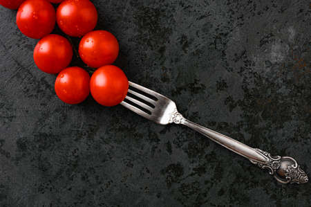 fork and tomatoes on a flat surface Reklamní fotografie - 153076379