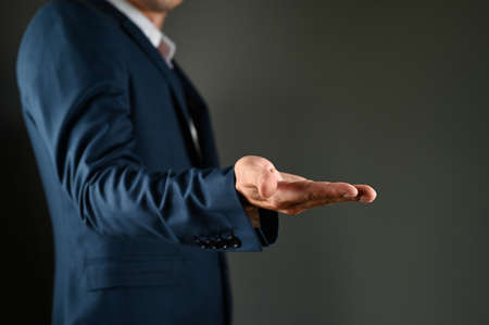 Man in a suit with outstretched arm imitating support. High quality photo Stock Photo