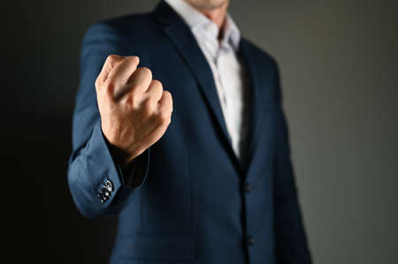 A man in a suit threatens with his fist. High quality photo