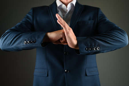 A man in a suit hits the palm with his fist. A man in a suit and a fist on a black background. Concept: construction in business. High quality photo Zdjęcie Seryjne