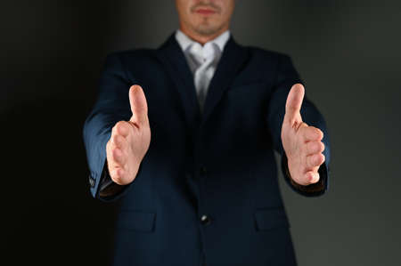 A man in a suit spreads his arms. A man in a suit spreads his arms to the side on a black background. Concept: building in business. High quality photo