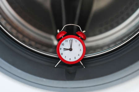 Washing machine and clock. Washing time concept