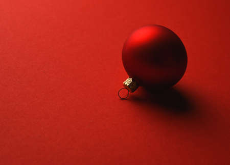 Red Christmas ball lies on a red surface with shadows