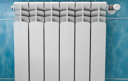 room white battery for heating on a blue background Reklamní fotografie