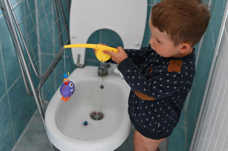 Child fishing at home in the bathroom Reklamní fotografie
