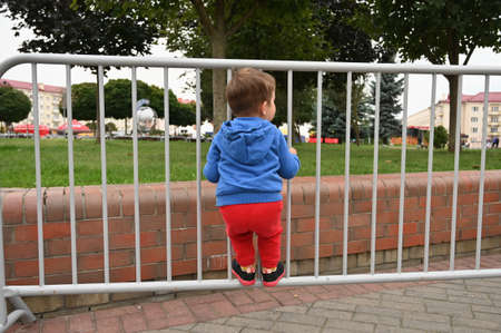 the child climbed the metal fence. High quality photo